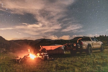 Stars behind pickup truck and bonfire