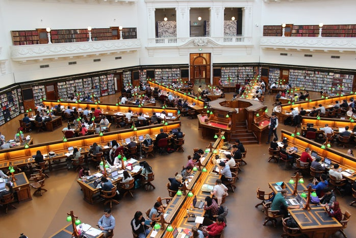 people studying and working side by side in large library