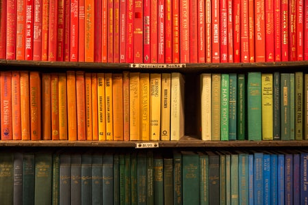 rainbow colored books on a shelf