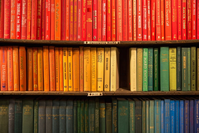 rainbow colored books on a shelf