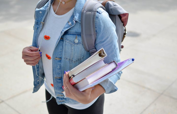 student carrying books and backpack
