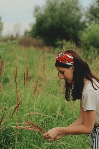 Girl picking up flower with bandana on the head