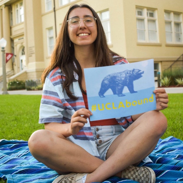 girl sitting on a towel, holding a #UCLAbound poster
