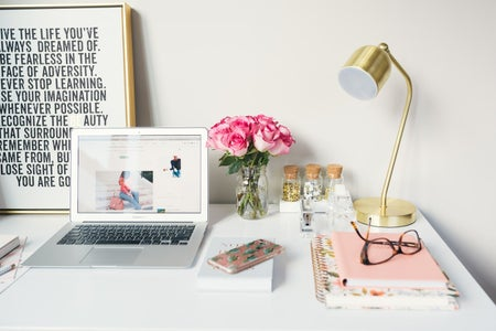 laptop open on white desk with pink and golden accents