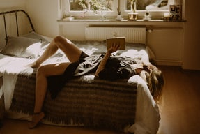 Woman reading a book in bedroom