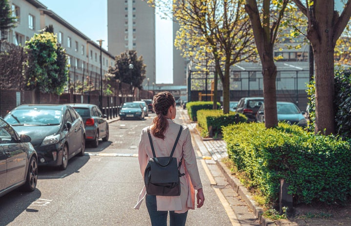 Photo of young brunette woman wearing a backpack and walking down a street alone shot from behind