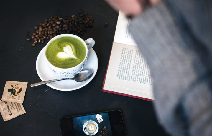 dark cafe desk with phone, matcha latte, and book.