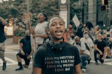 "Young person in a shirt that says ""I love my history, i love my people"""