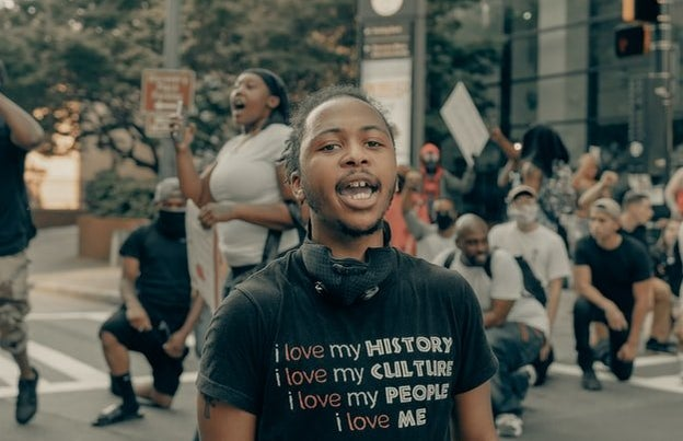 """Young person in a shirt that says \""""I love my history, i love my people\"""""""