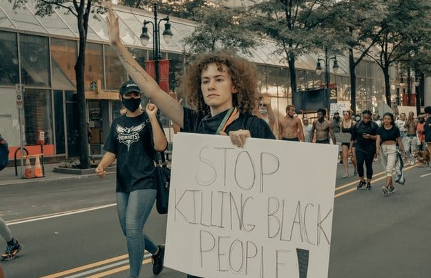"""Protester holding sign that says \""""stop killing black people\"""""""