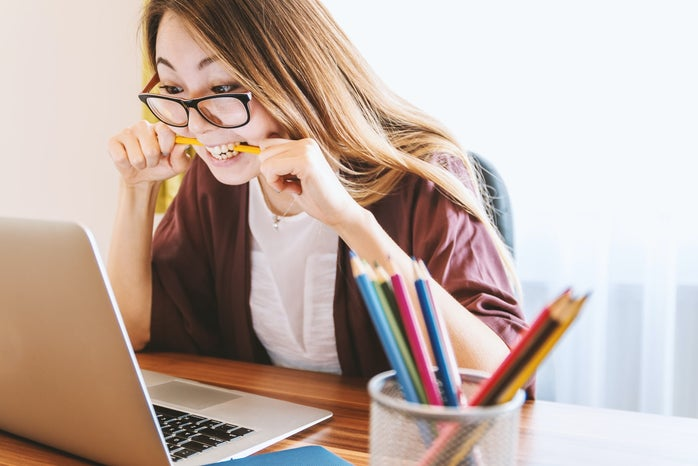 woman with glasses biting pencil while looking at laptop
