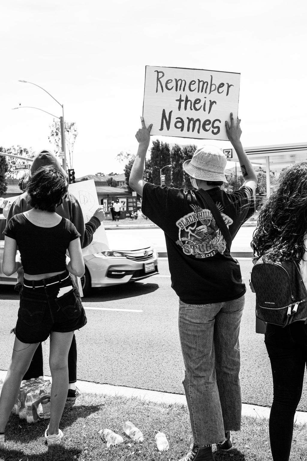 """Protester with \""""Remember their Names\"""" sign"""