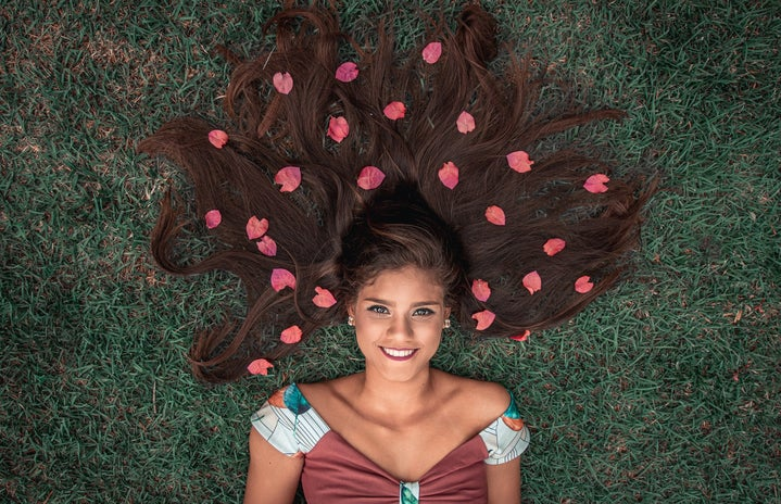 Woman laying in grass, flowers in her hair