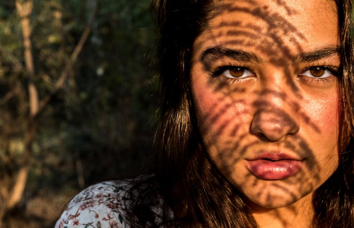 Woman with plant shadows on her face