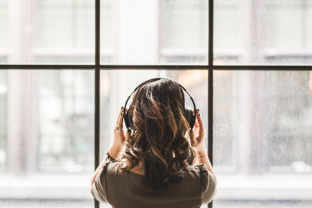 brunette woman shot from behind facing a window, wearing headphones listening to music and holding them with her hands