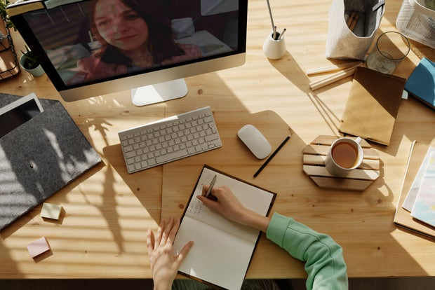 overhead shot of a desk with someone writing in a notebook and on a video call on a computer