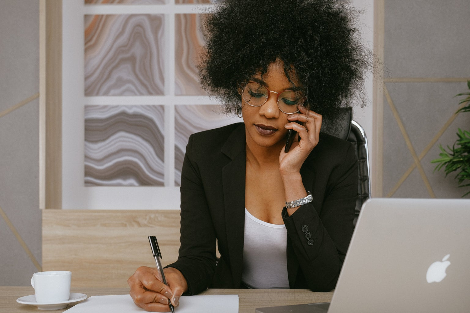 woman in black blazer on the phone taking notes