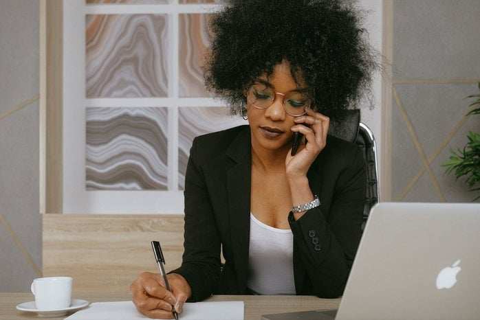 woman wearing blazer taking notes on the phone