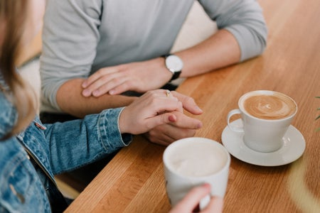 couple holding hands while drinking coffee at table