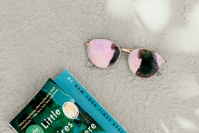 little fires everywhere book next to sunglasses