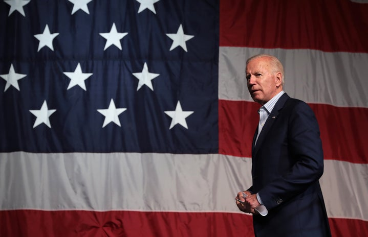 Joe Biden speaking in front of an American flag