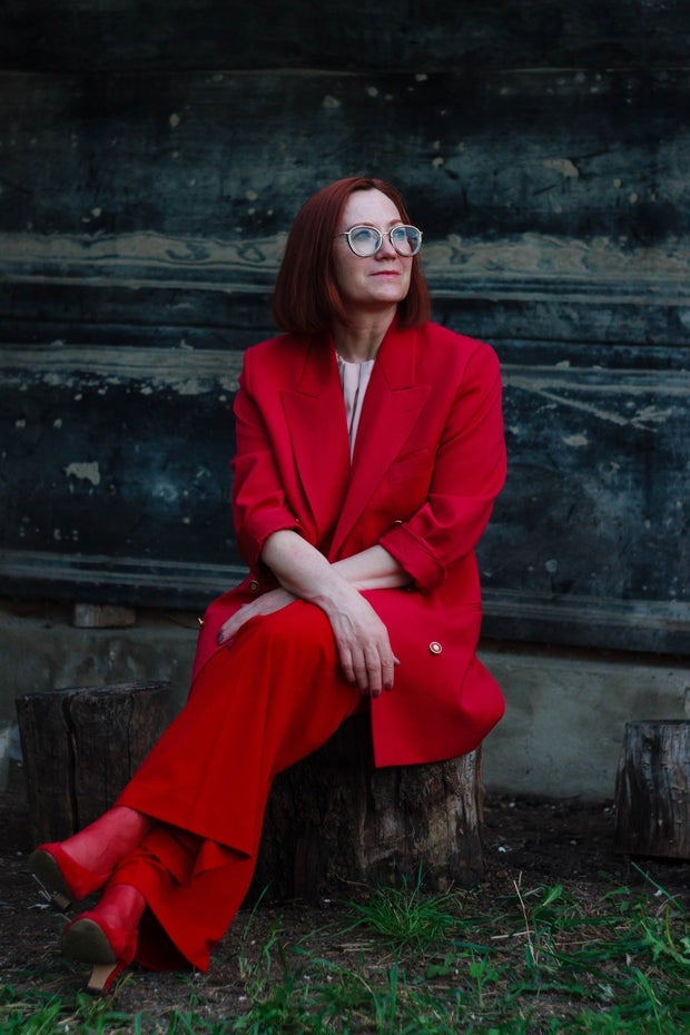 woman in red suit with glasses sitting on tree stump