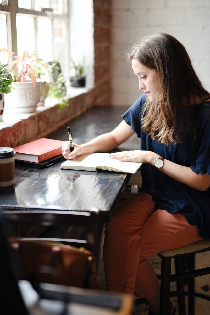 Woman sitting at a black table writing on a notebook.