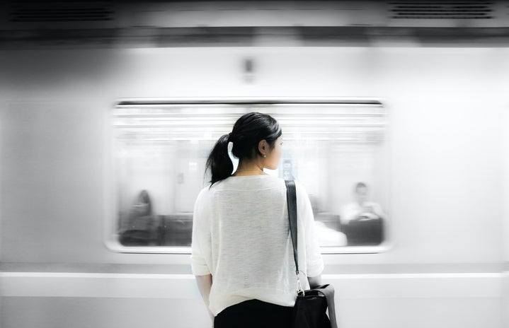 woman standing in front of moving subway train