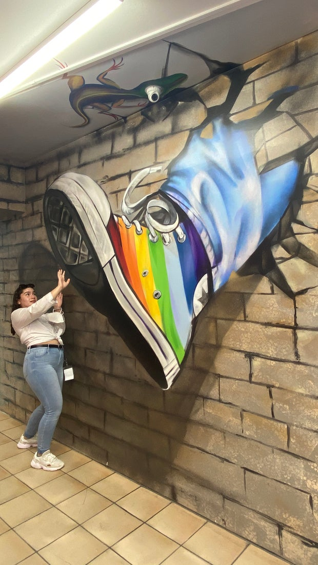 Girl posing with a art wall illusion of a colorful shoe.