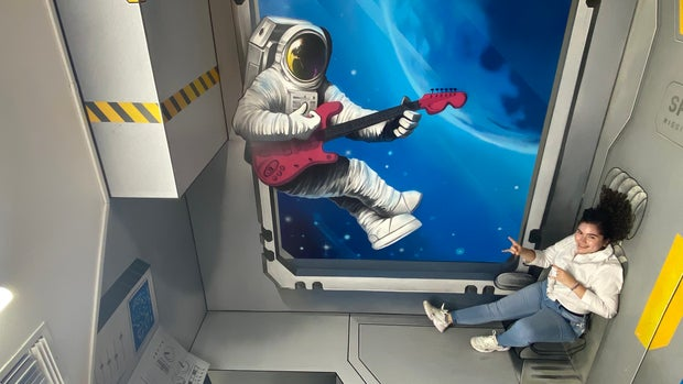 Girl posing with an art wall illusion of an astronaut in space