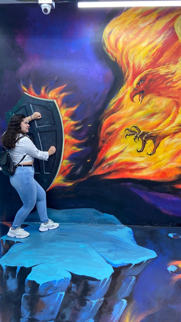 Girl posing with art wall illusion of a firebird and a shield