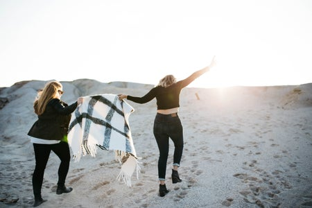 "alt=""vignette photography of two woman holding scarf walking on sand"""