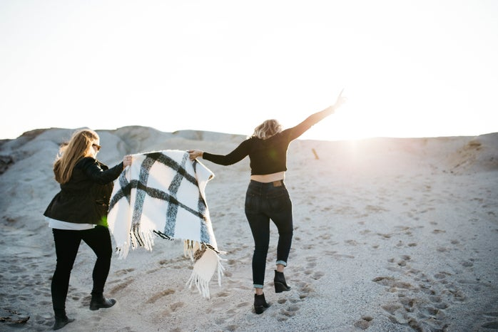 """alt=""""vignette photography of two woman holding scarf walking on sand"""""""