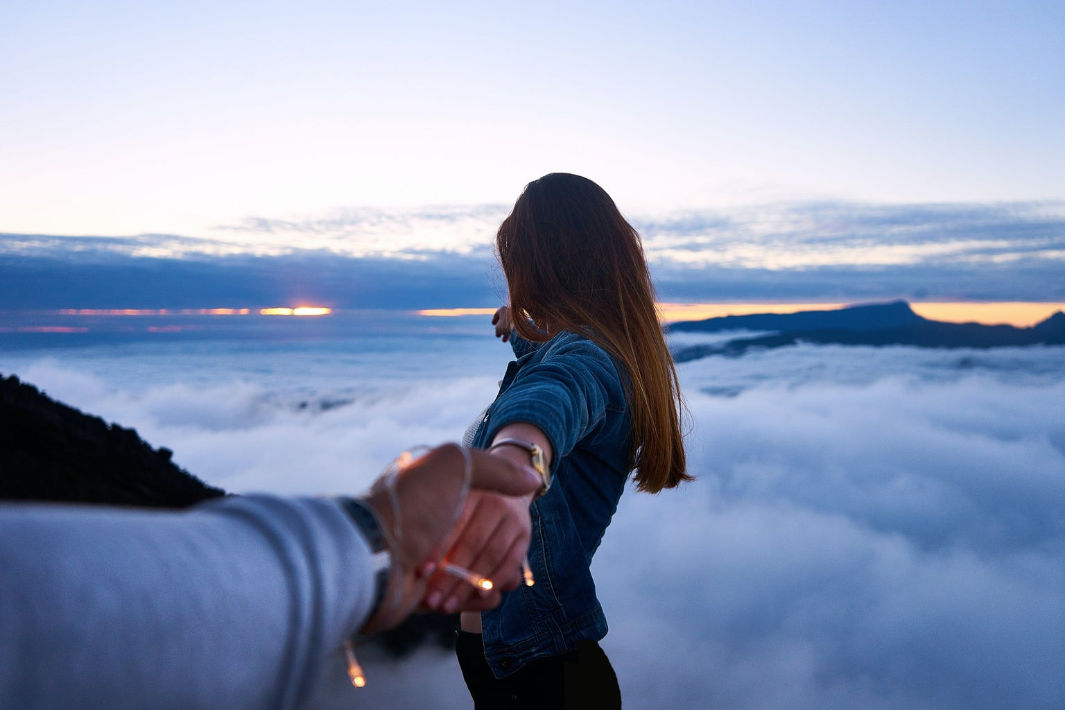 person holding woman\'s hand on top of hill