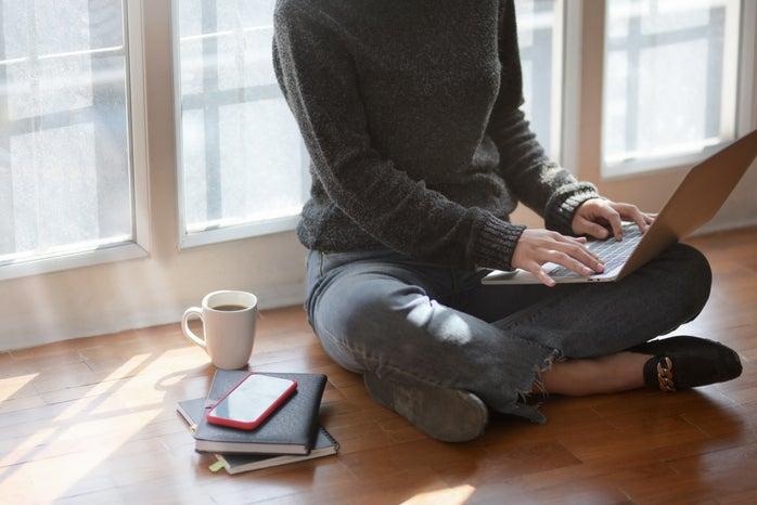 Woman with laptop beside window