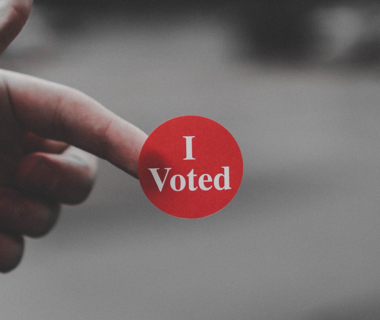 """Hand holding a red sticker with the words """"I Voted"""""""