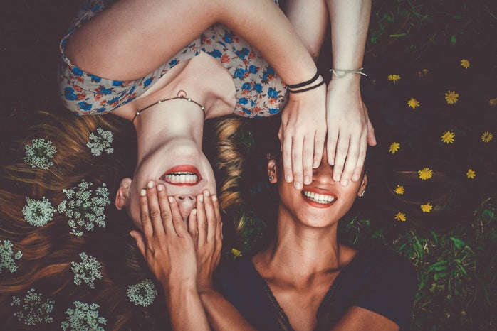 two woman smiling while laying on lawn field and covering each other\'s eyes