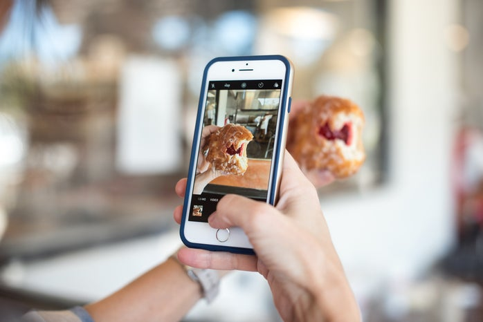 selective focus photography of person taking picture of jelly donut