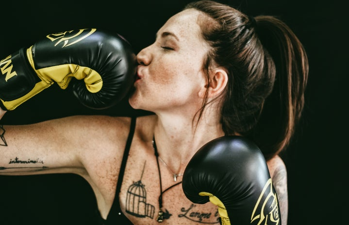 woman kissing black leather boxing gloves