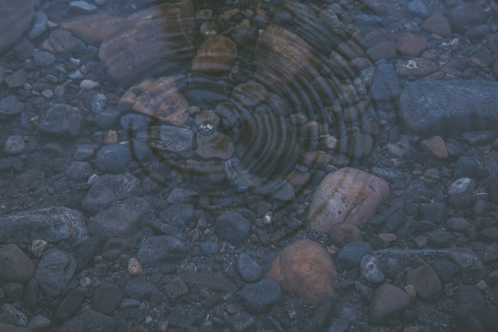 ripple on crystal clear water revealing smooth stones beneath the surface