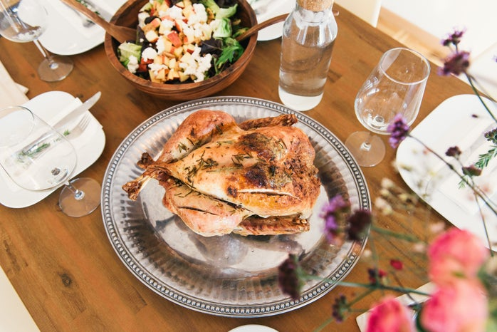 roasted chicken on a wooden table with sides and place settings