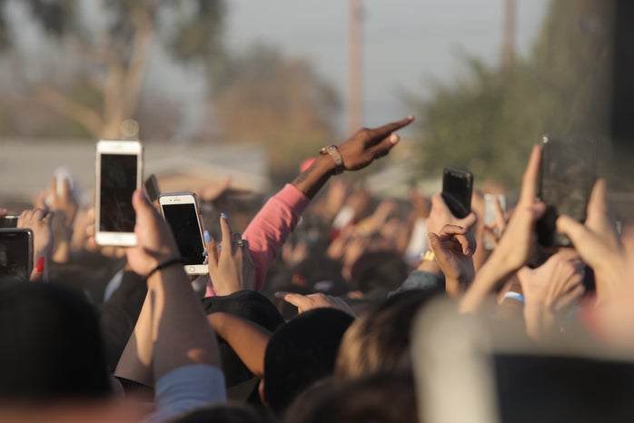 people holding smartphones in a crowd