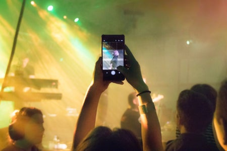 person taking a a photo with phone at a concert