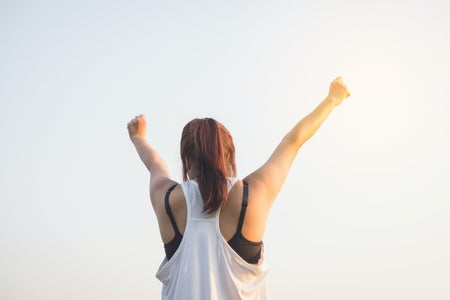 woman raising her hands in victory