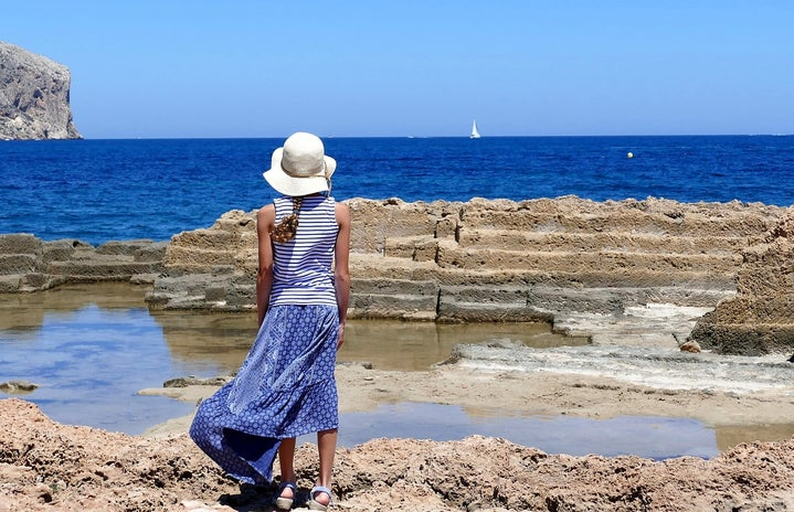 woman in blue dress and white hat facing the ocean