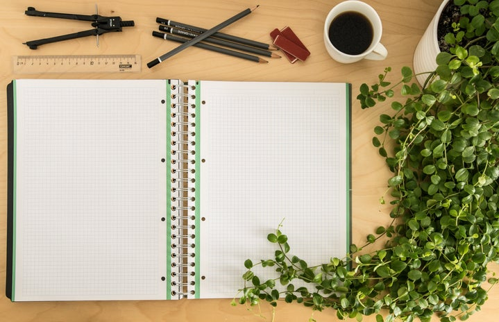 green and white grid notebook on desk with pencils, coffee, and plant