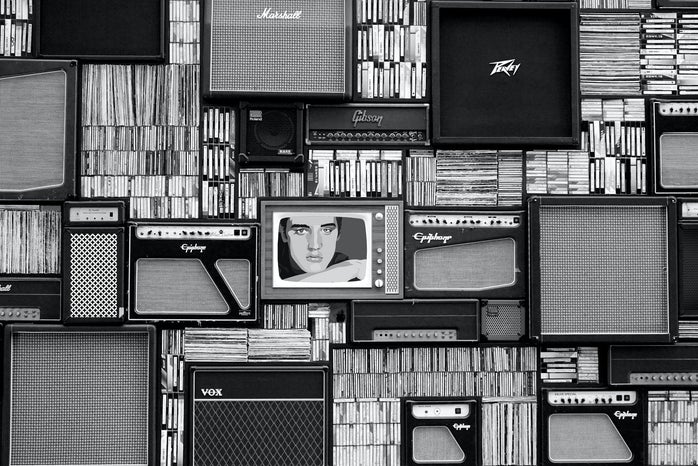 black and white wall of records, speakers, and a TV in the center with the image of Elvis Presley
