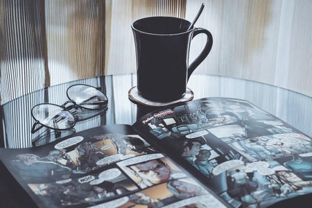 a comic book and a pair of glasses on a table