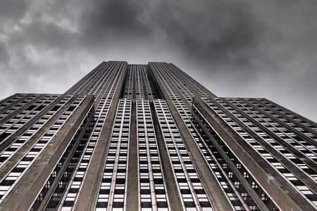 low angle photo of tall building against stormy sky