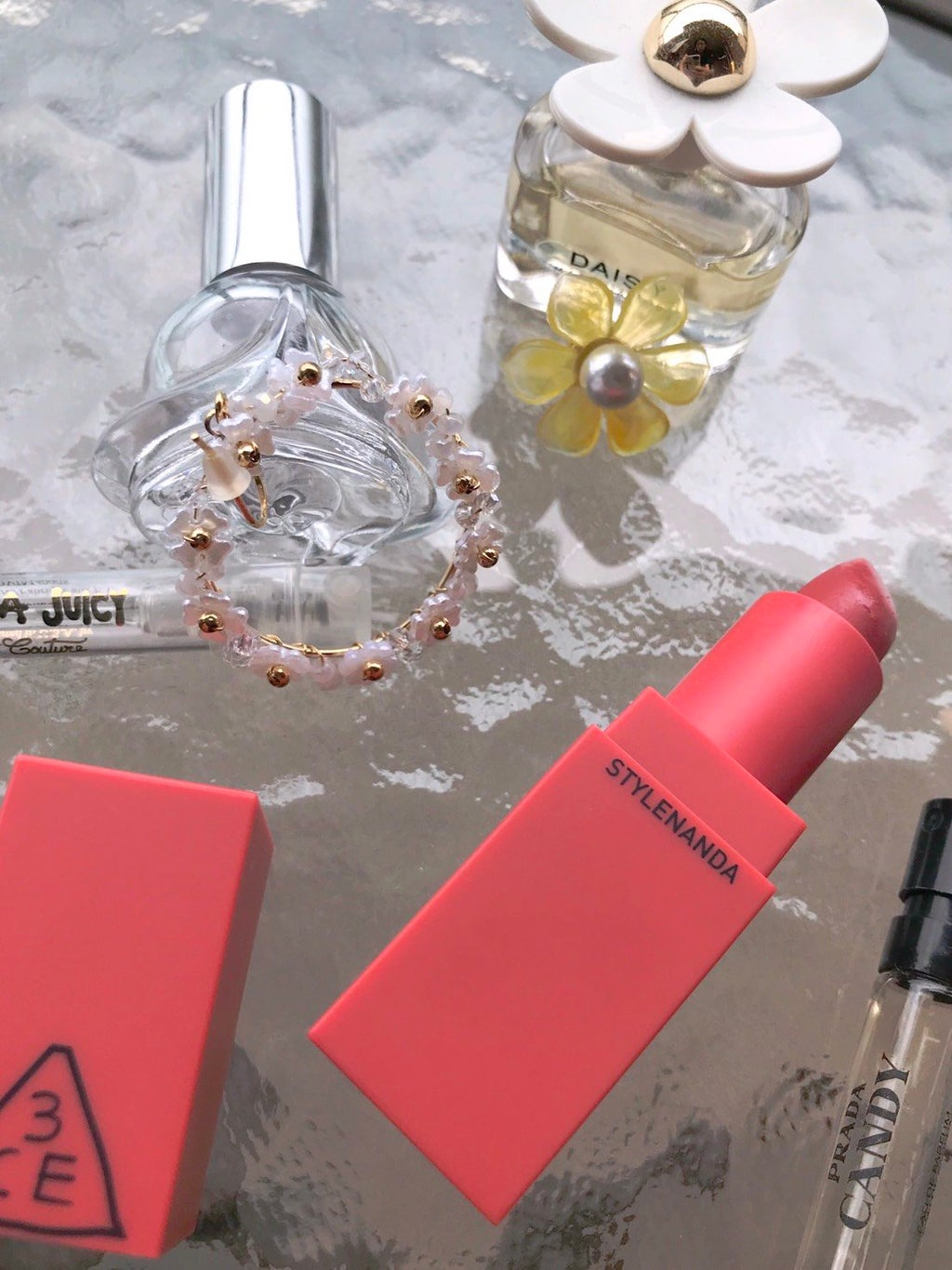 flatlay image of perfumes, earrings, and 3CE coral lipstick